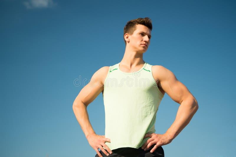 Άτομο bodybuilder που θέτει στο μπλε ουρανό στοκ φωτογραφία με δικαίωμα ελεύθερης χρήσης