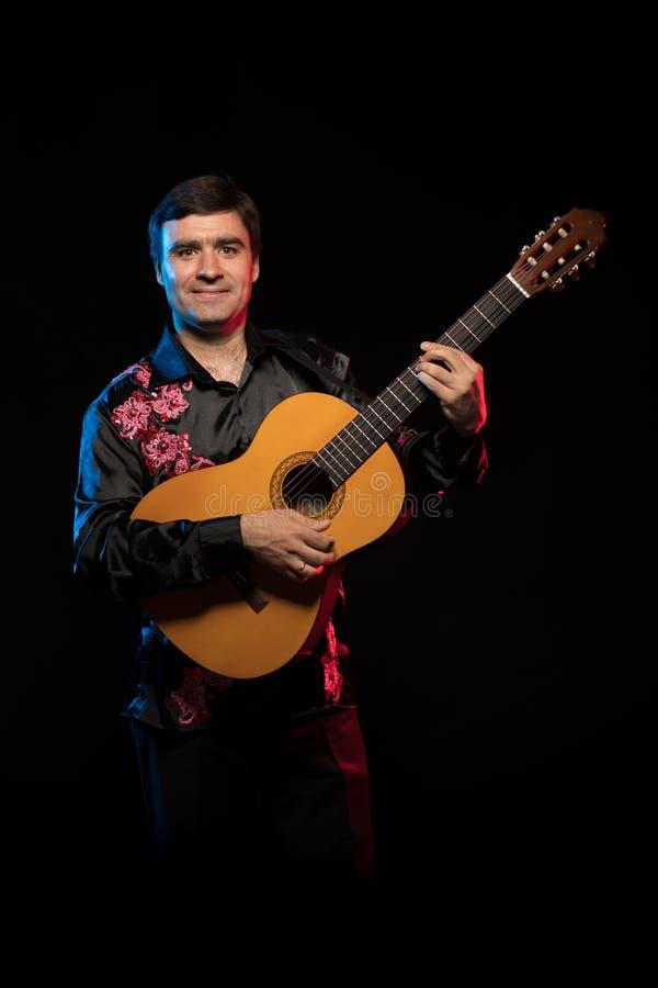 Άτομο Brunette μουσικών καλλιτεχνών σε ένα μαύρο πουκάμισο που παίζει την κιθάρα στοκ φωτογραφία