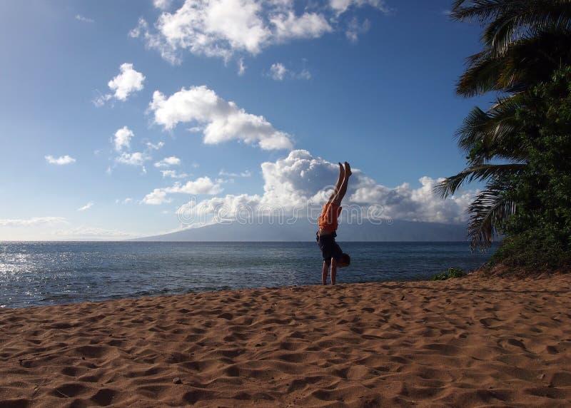 Άτομο Handstands στην παραλία σε Maui στοκ εικόνες