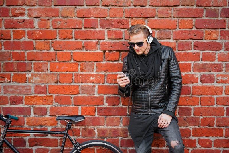 Άτομο Hipster με το ποδήλατο που υπερασπίζεται το τουβλότοιχο και που ακούει τη μουσική στοκ εικόνες