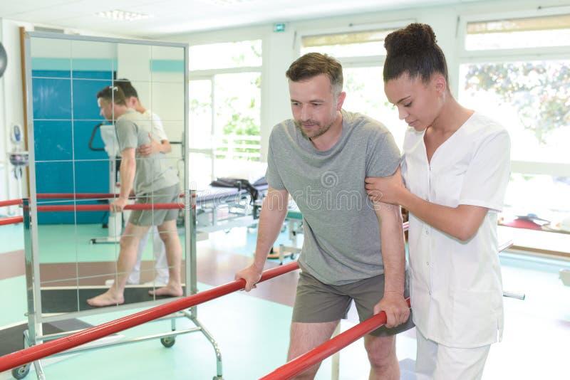 Άτομο treadmill με το σκύψιμο θεραπόντων στο στούντιο ικανότητας στοκ εικόνες