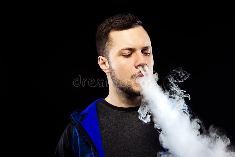Άτομο Vaping και ένα σύννεφο του ατμού στοκ φωτογραφία με δικαίωμα ελεύθερης χρήσης