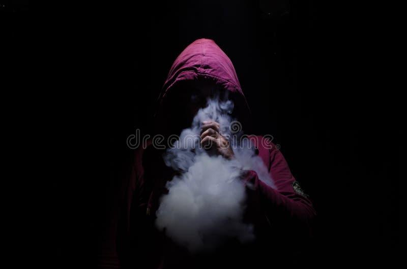 Άτομο Vaping που κρατά έναν νεαρό δικυκλιστή Ένα σύννεφο του ατμού Μαύρη ανασκόπηση Vaping ένα ηλεκτρονικό τσιγάρο με πολύ καπνό στοκ φωτογραφία με δικαίωμα ελεύθερης χρήσης