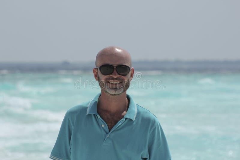Άτριχο μέσης ηλικίας άτομο στην παραλία στοκ εικόνες