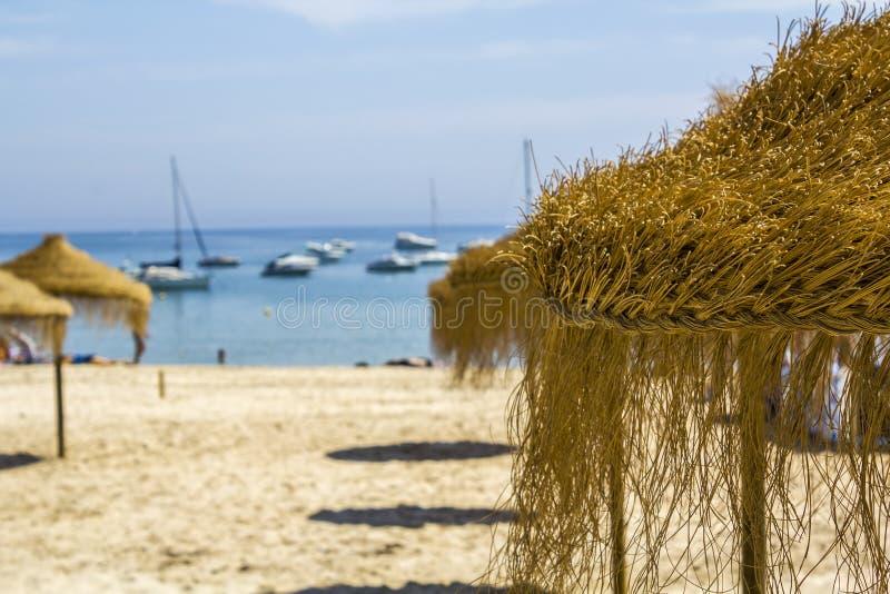 Άχυρο parasols σε μια αμμώδη παραλία με τα γιοτ που πλέουν με το υπόβαθρο στοκ φωτογραφίες με δικαίωμα ελεύθερης χρήσης