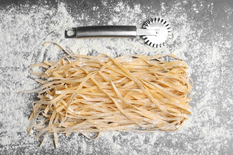 Άψητα νουντλς, αλεύρι και μαχαίρι στον πίνακα στοκ φωτογραφία