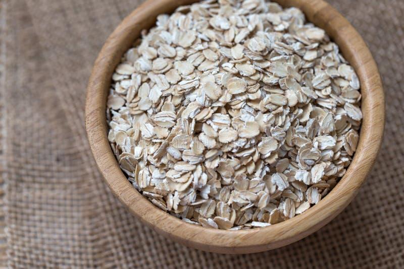 Άψητες oatmeal ή βρωμών νιφάδες σε ένα ξύλινο κύπελλο στοκ φωτογραφία με δικαίωμα ελεύθερης χρήσης