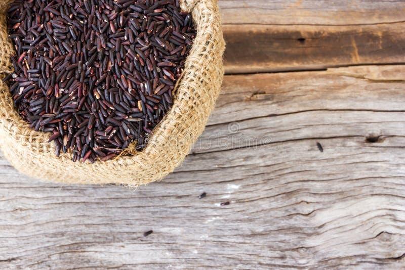 Άψητο ρύζι σε έναν μικρό burlap σάκο μαύρο ρύζι στοκ εικόνες
