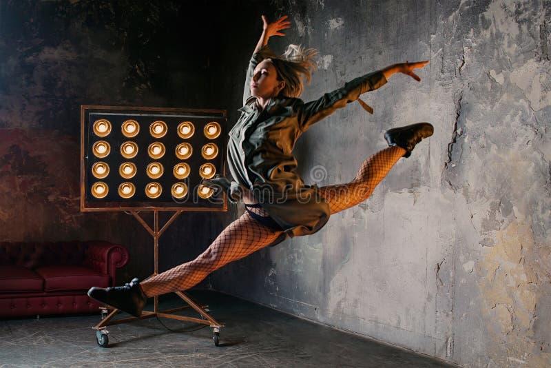 Άλμα χορευτών γυναικών υψηλό στη σοφίτα στοκ φωτογραφίες