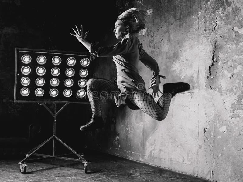 Άλμα χορευτών γυναικών υψηλό στη σοφίτα στοκ φωτογραφία