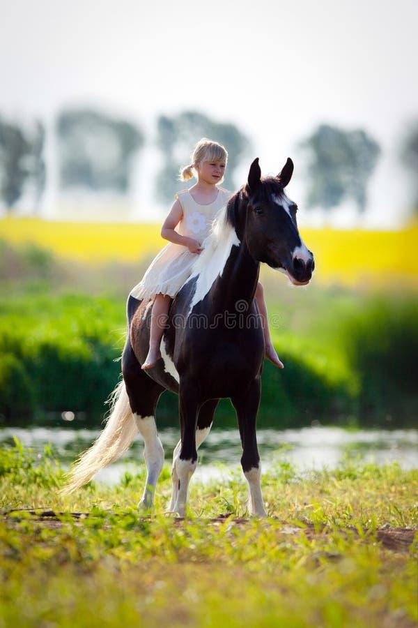 Άλογο οδήγησης παιδιών στο λιβάδι στοκ εικόνα με δικαίωμα ελεύθερης χρήσης