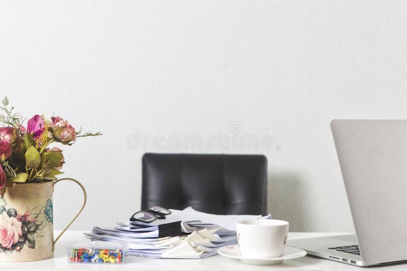 Έγγραφα, lap-top, και φλυτζάνι καφέ στον πίνακα γραφείων γραφείων στην άσπρη οθόνη στοκ φωτογραφίες