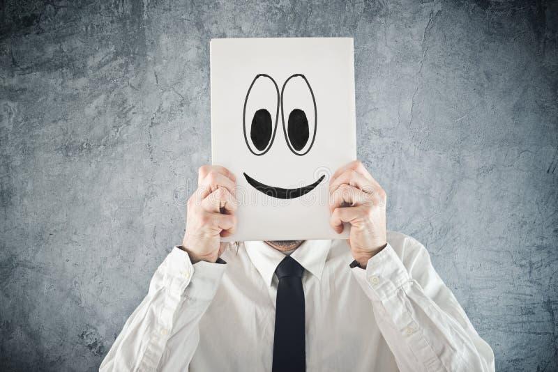 Έγγραφο εκμετάλλευσης επιχειρηματιών με το πρόσωπο smiley μπροστά από το κεφάλι του στοκ εικόνα