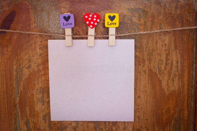 Έγγραφο με τα clothespins με τις καρδιές που κρεμούν από ένα σχοινί στοκ φωτογραφίες