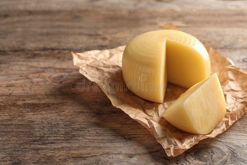 Έγγραφο περγαμηνής με την κομμένη ρόδα του εύγευστου τυριού στον ξύλινο πίνακα Διάστημα για στοκ φωτογραφία