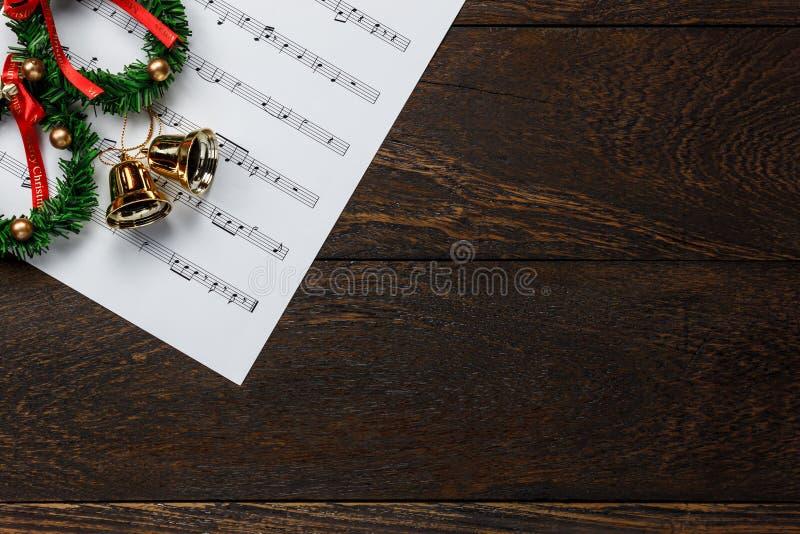Έγγραφο σημειώσεων μουσικής Χριστουγέννων με το στεφάνι Χριστουγέννων στο wo στοκ φωτογραφίες