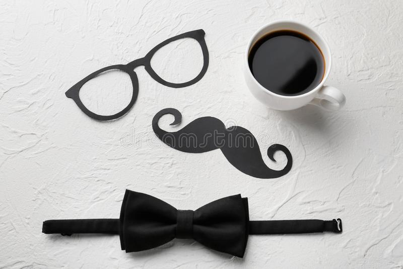 """Έγγραφο mustache, γυαλιά, δεσμός τόξων και φλιτζάνι του καφέ στο άσπρο κατασκευασμένο υπόβαθρο Εορτασμός ημέρας πατέρων \ """"s στοκ εικόνα με δικαίωμα ελεύθερης χρήσης"""