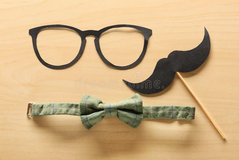Έγγραφο mustache, γυαλιά και δεσμός τόξων στο ξύλινο υπόβαθρο Εορτασμός ημέρας πατέρα στοκ φωτογραφίες
