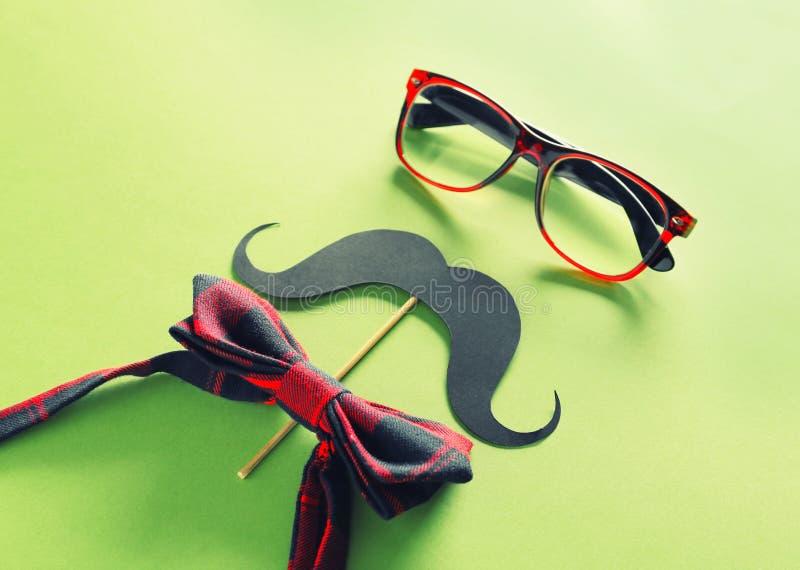 Έγγραφο mustache, γυαλιά και δεσμός τόξων στο υπόβαθρο χρώματος Εορτασμός ημέρας πατέρα στοκ εικόνες