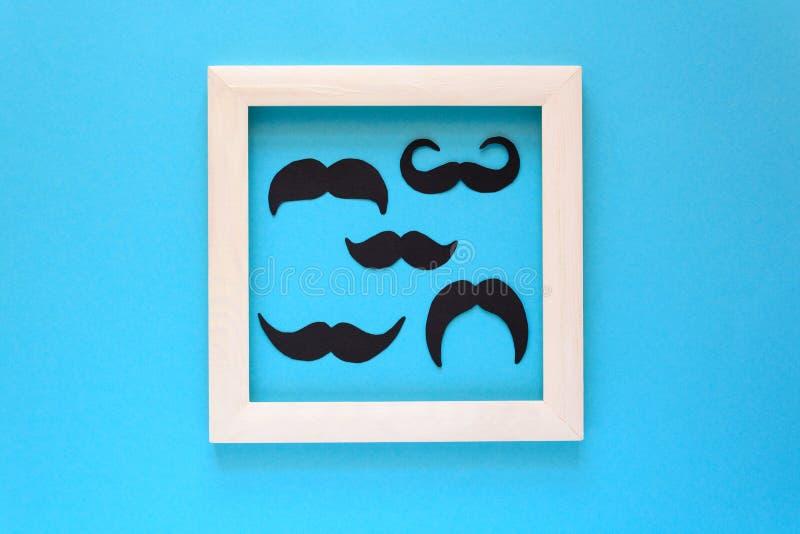 Έγγραφο mustache στο άσπρο ξύλινο πλαίσιο στο μπλε υπόβαθρο εγγράφου Αποκομμένο ύφος movember έννοια στοκ εικόνα