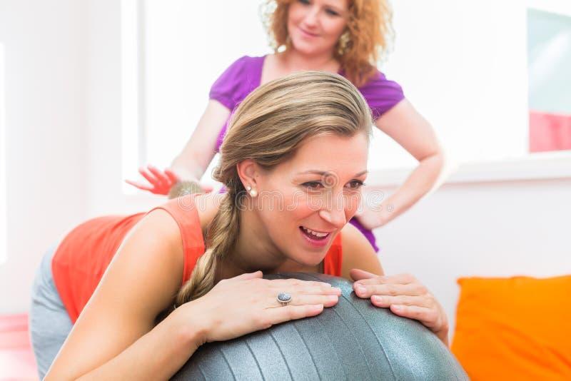Έγκυες νέες γυναίκες που παίρνουν backrub με την ακιδωτή σφαίρα μασάζ στοκ εικόνες