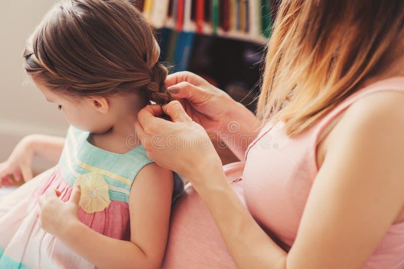 Έγκυες πλεξούδες ύφανσης μητέρων στην κόρη μικρών παιδιών της στο σπίτι στοκ εικόνα με δικαίωμα ελεύθερης χρήσης