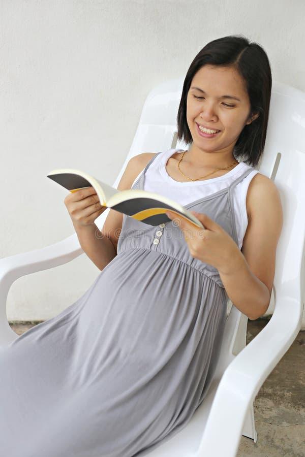 Έγκυοι γυναίκες της Ασίας ευτυχώς στην ανάγνωση ενός βιβλίου στοκ φωτογραφίες