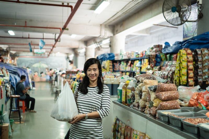 Έγκυος ασιατική νέα γυναίκα που στέκεται φέρνοντας τη πλαστική τσάντα στοκ εικόνα
