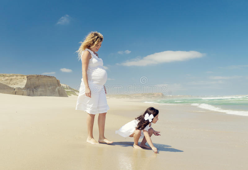 Έγκυος γυναίκα και η κόρη της στην παραλία στοκ φωτογραφίες με δικαίωμα ελεύθερης χρήσης