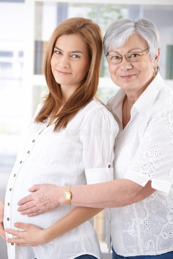 Έγκυος γυναίκα και μητέρα που χαμογελούν ευτυχώς στοκ φωτογραφία με δικαίωμα ελεύθερης χρήσης