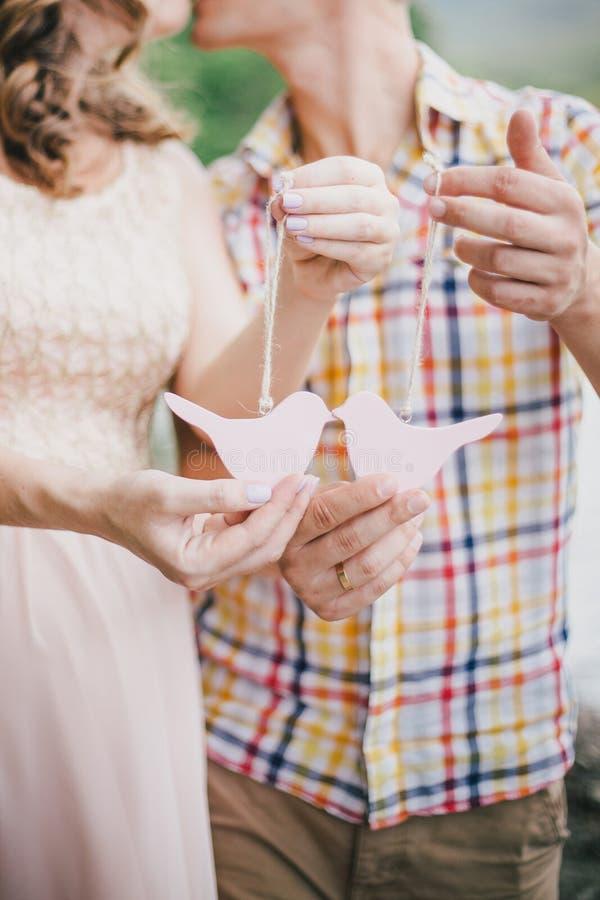 Έγκυος γυναίκα με τα πουλιά παιχνιδιών εκμετάλλευσης συζύγων της στα χέρια τους στοκ φωτογραφίες με δικαίωμα ελεύθερης χρήσης