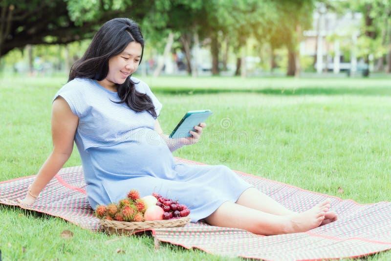 Έγκυος γυναίκα με τη χαλάρωση ταμπλετών στον κήπο στοκ φωτογραφία