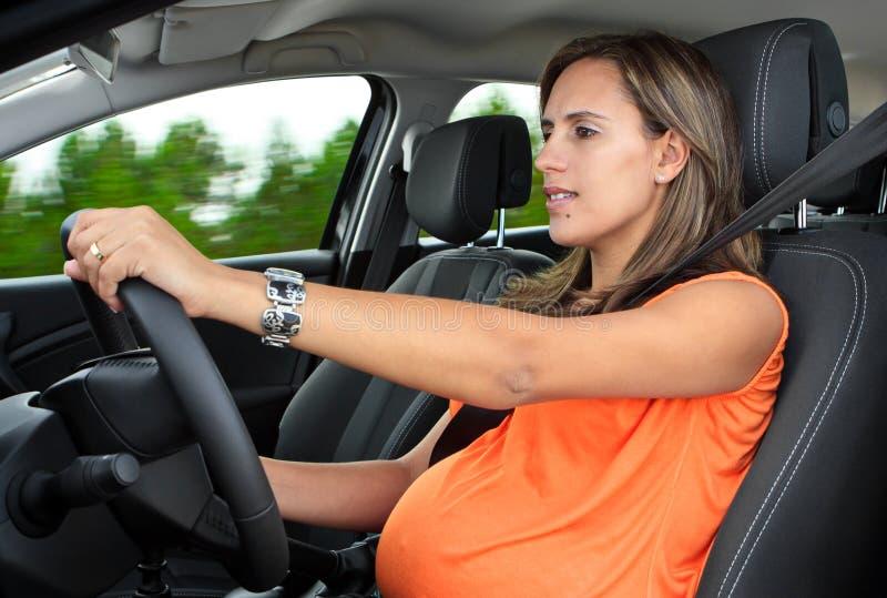 Έγκυος γυναίκα που ένα αυτοκίνητο στοκ φωτογραφία