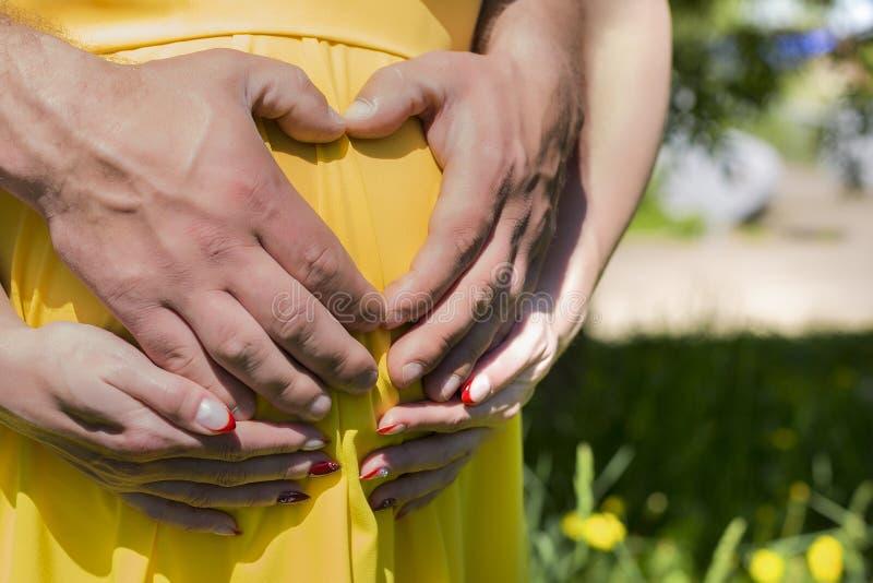 Έγκυος γυναίκα που αγκαλιάζει το σύζυγό της στην κοιλιά στοκ φωτογραφία με δικαίωμα ελεύθερης χρήσης