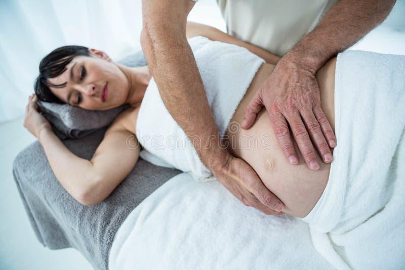 Έγκυος γυναίκα που λαμβάνει ένα μασάζ στομαχιών από το μασέρ στοκ εικόνες με δικαίωμα ελεύθερης χρήσης