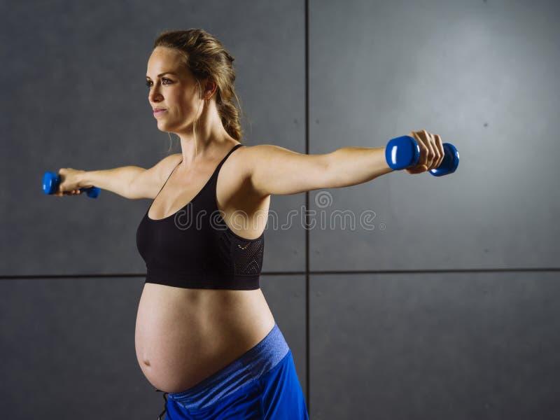 Έγκυος γυναίκα που ασκεί με τους αλτήρες στοκ φωτογραφία με δικαίωμα ελεύθερης χρήσης