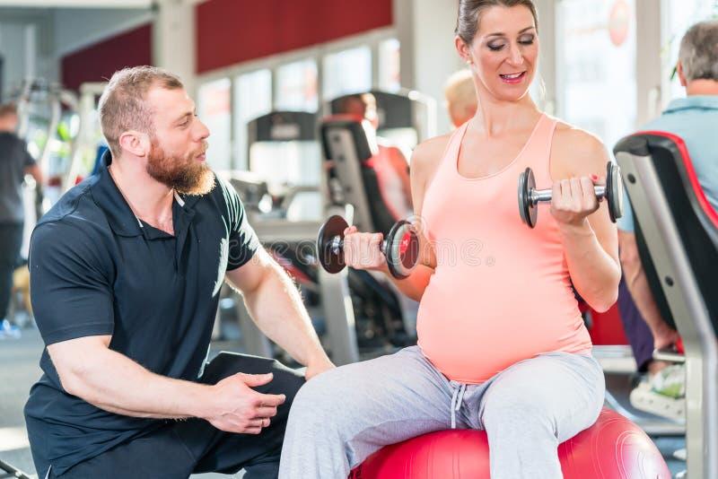 Έγκυος γυναίκα που επιλύει με τον προσωπικό εκπαιδευτή στη γυμναστική στοκ εικόνα