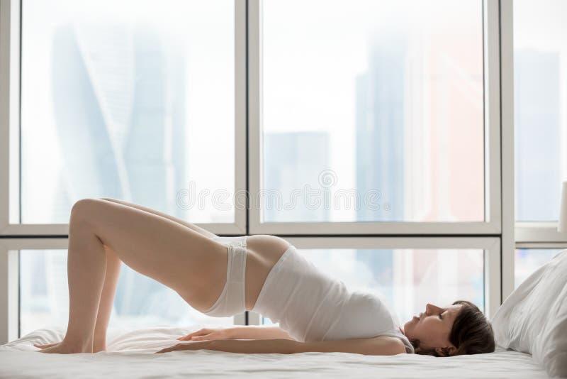 Έγκυος γυναίκα που κάνει την άσκηση γεφυρών ώμων στοκ φωτογραφίες