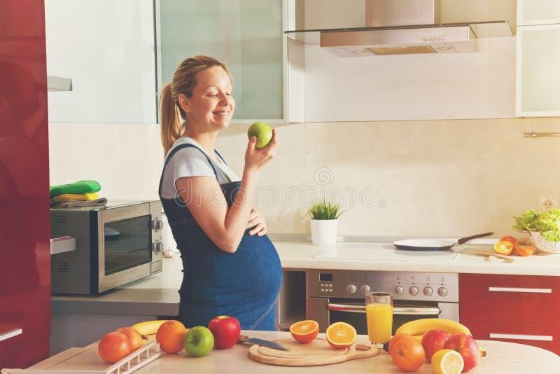 έγκυος γυναίκα που κατασκευάζει τον υγιή χυμό φρούτων και που τρώει το μήλο στοκ εικόνες