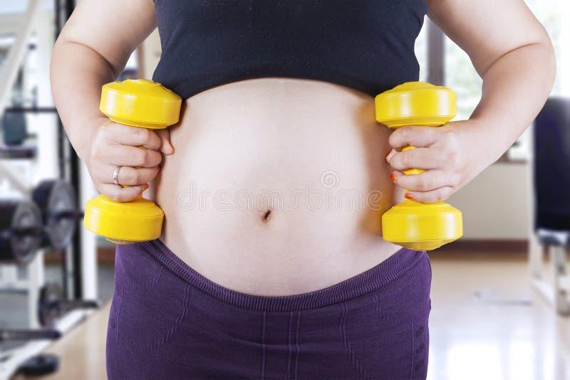 Έγκυος γυναίκα που κρατά δύο αλτήρες στοκ εικόνες με δικαίωμα ελεύθερης χρήσης