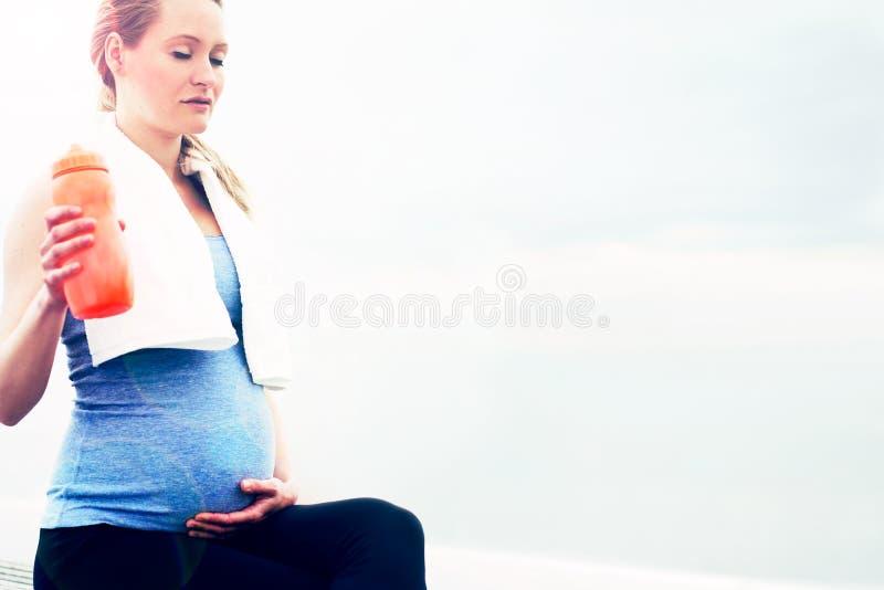 Έγκυος γυναίκα που παίρνει ένα σπάσιμο από την άσκησή της στοκ φωτογραφία με δικαίωμα ελεύθερης χρήσης