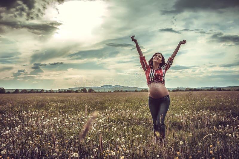 Έγκυος γυναίκα που χαλαρώνει έξω στοκ φωτογραφία