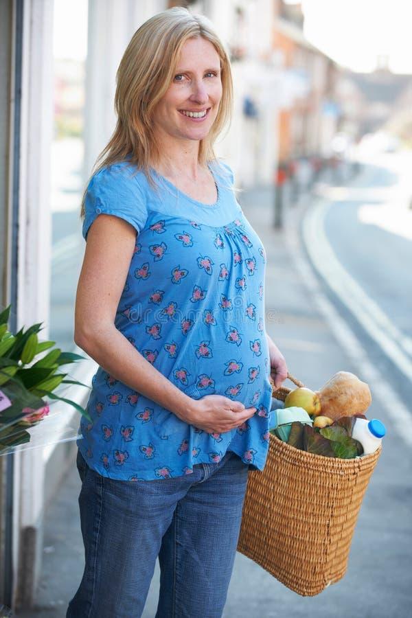 Έγκυος γυναίκα που ψωνίζει για τα παντοπωλεία στοκ φωτογραφία