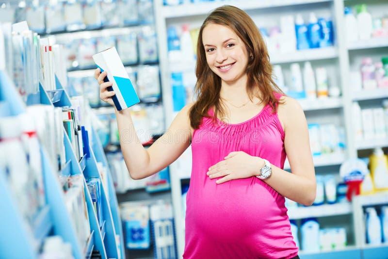 Έγκυος γυναίκα που ψωνίζει στο κατάστημα καλλυντικών στοκ εικόνες