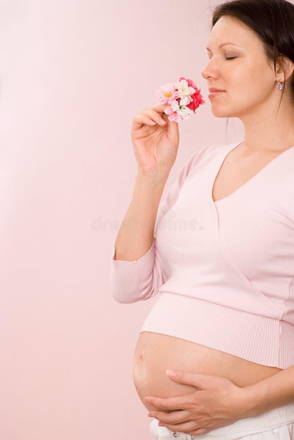 Έγκυος γυναίκα σε ένα ροζ στοκ φωτογραφία
