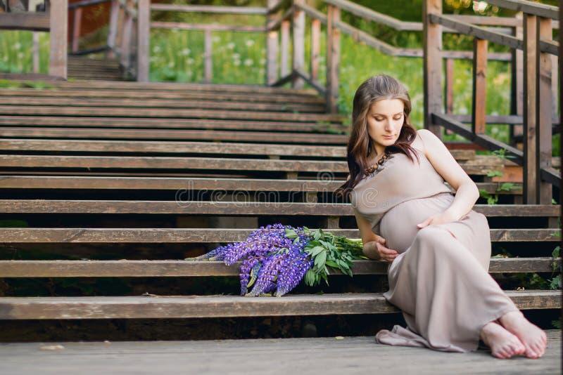 Έγκυος γυναίκα στα σκαλοπάτια στο πάρκο στοκ φωτογραφίες
