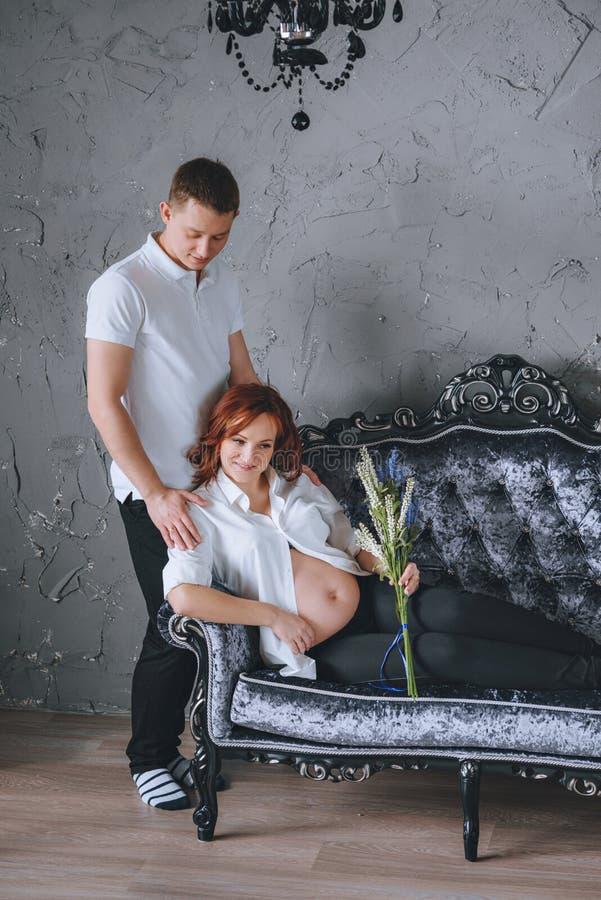 Έγκυος γυναίκα στον γκρίζο καναπέ Στάση δίπλα στο σύζυγό της στοκ φωτογραφία