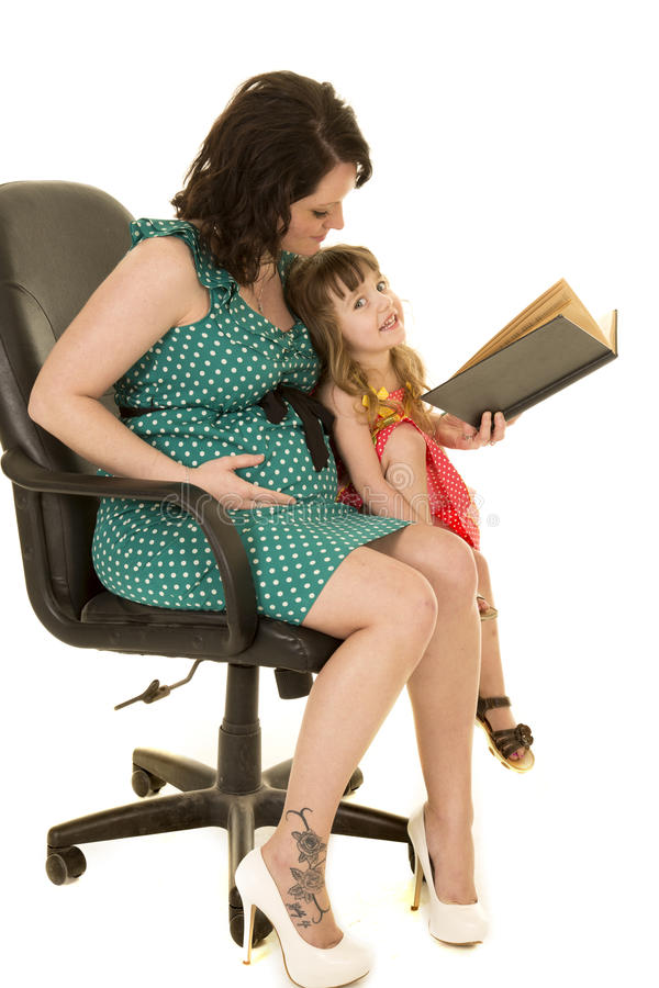Έγκυος γυναίκα στο πράσινο φόρεμα που διαβάζεται στο παιδί στοκ εικόνες με δικαίωμα ελεύθερης χρήσης
