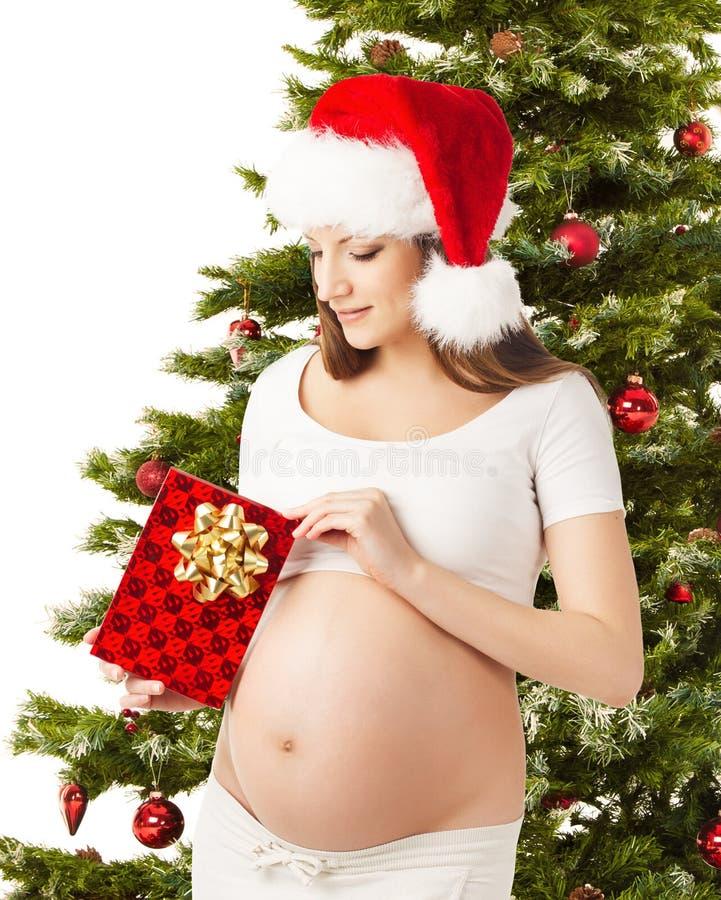 Έγκυος γυναίκα Χριστουγέννων στο καπέλο Santa, το παρόντα κιβώτιο δώρων και το έλατο στοκ φωτογραφία