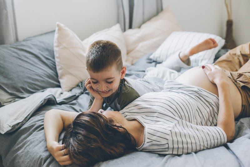 Έγκυος μητέρα που παίζει με παιδί στην κρεβατοκάμαρα στοκ εικόνες